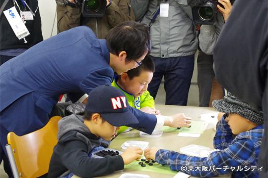 子供たちが対局している部屋で直接アドバイスをしながら見回りをする井山裕太さん。