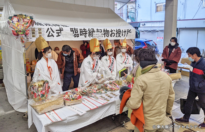 熊手飾や福よせ等のお授け物は布施商店街内のコンビニの前で福娘さんたちがお授けしていました